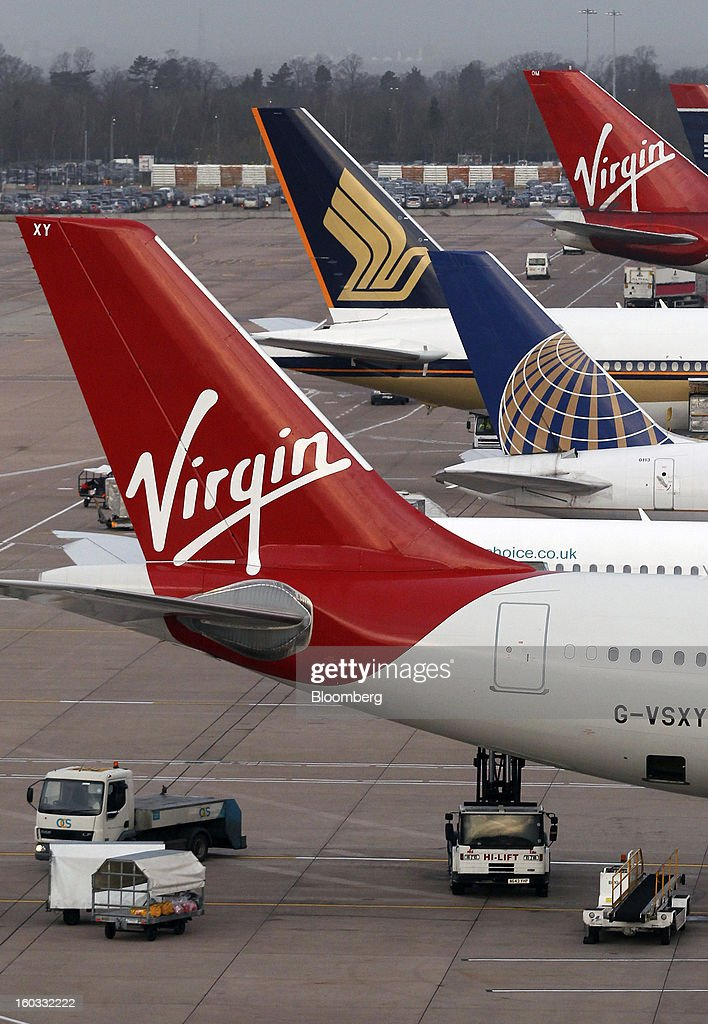 Logos sit on the tailfins of aircraft operated by Virgin Atlantic, United Continental Holdings Inc. and Singapore Airlines, sit parked at the gates of terminal two at Manchester airport in Manchester, U.K., on Tuesday, Jan. 29, 2013. Manchester Airports Group, owner of Britain's busiest airport outside London, is buying Stansted from Heathrow Airport Ltd., which is ceding 100 percent of Stansted to comply with regulatory requirements. Photographer: Paul Thomas/Bloomberg via Getty Images