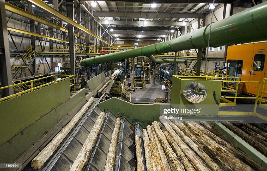 Logs move along the production line at the West Fraser Timber Co. sawmill in Quesnel, British Columbia, Canada, on Thursday, July 11, 2013. West Fraser Timber Co., the largest lumber producer in North America, had a sustainable rise in price, demand volatility, and profits within the past year. Photographer: Ben Nelms/Bloomberg via Getty Images
