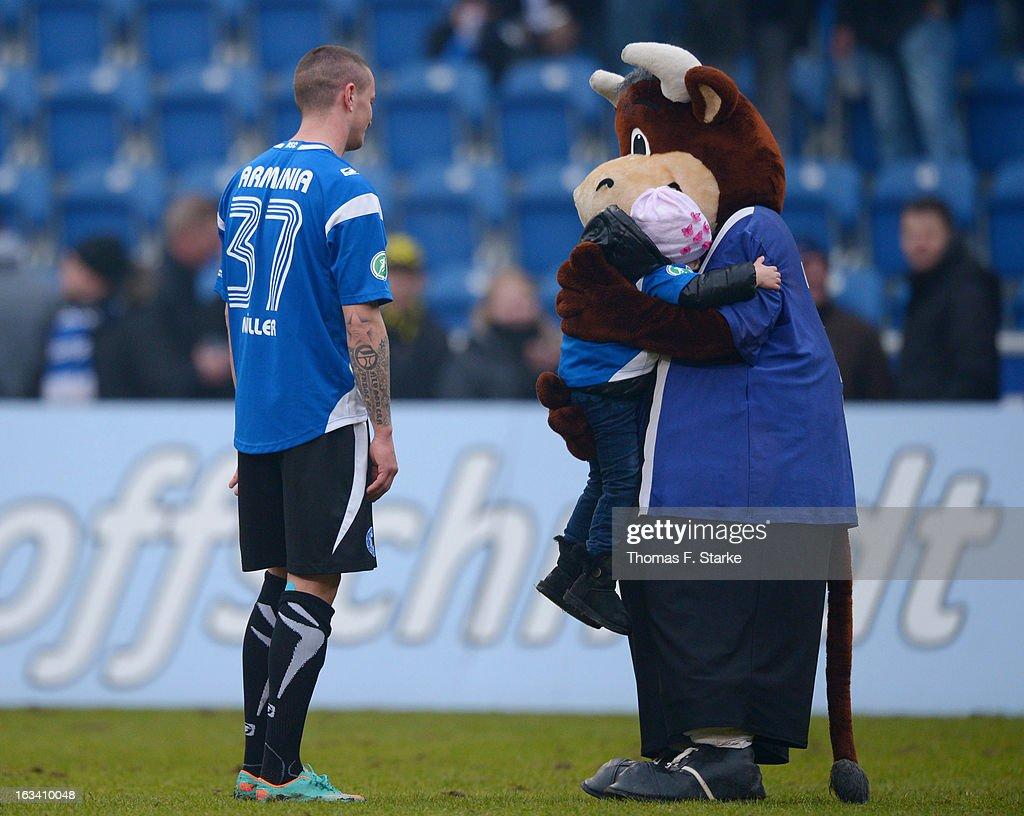Lohmann (R), the Bielefeld Mascot hugs the child of Bielefeld player <a gi-track='captionPersonalityLinkClicked' href=/galleries/search?phrase=Christian+Mueller&family=editorial&specificpeople=645410 ng-click='$event.stopPropagation()'>Christian Mueller</a> (L) after the Third League match between Arminia Bielefeld and Preussen Muenster at Schueco Arena on March 9, 2013 in Bielefeld, Germany.