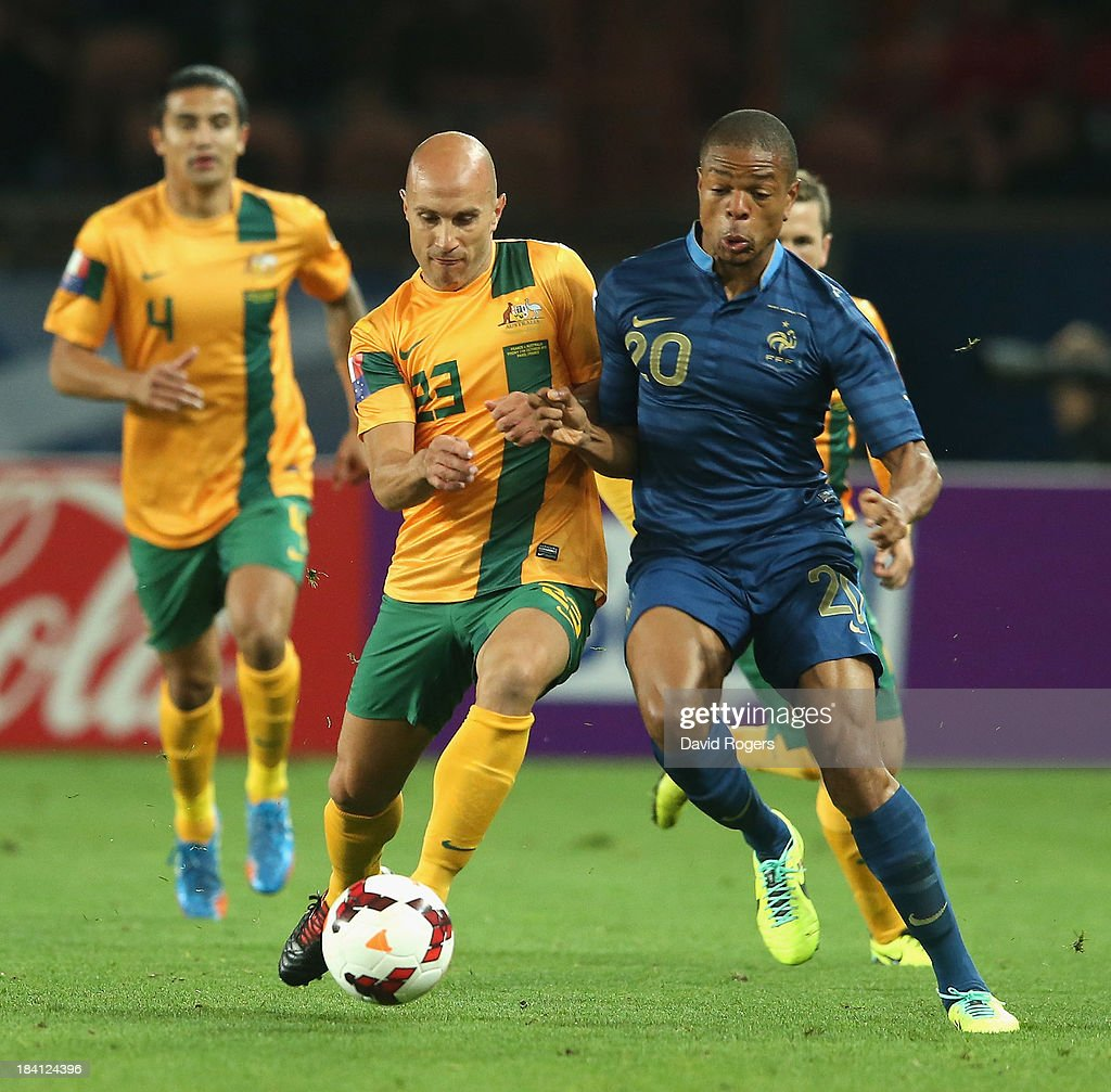 Loic Remy of France is challenged by Mark Bresciano during the International Friendly match between France and Australia at Parc des Princes on October 11, 2013 in Paris, France.