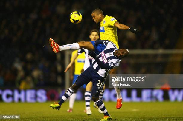 Loic Remy of Newcastle United challenges for the ball with Youssouf Mulumbu of West Bromwich Albion during the Barclays Premier League match between...