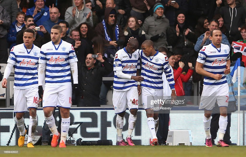 Loic Remy of Queens Park Rangers (second right) celebrates scoring a late goal with team mate Stephane Mbia during the Barclays Premier League match between Queens Park Rangers and Wigan Athletic at Loftus Road on April 7, 2013 in London, England.