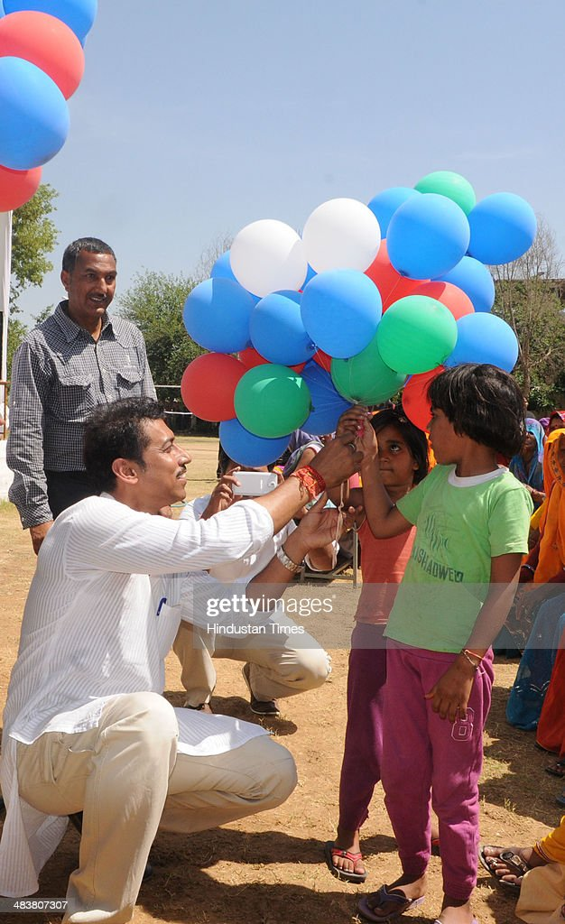 BJP Lok Sabha candidate for Jaipur Rural Constituency, Colonel Rajyavardhan Singh Rathore hands over balloons to kids while campaigning in Kukas village on April 10, 2014 in Jaipur, India.