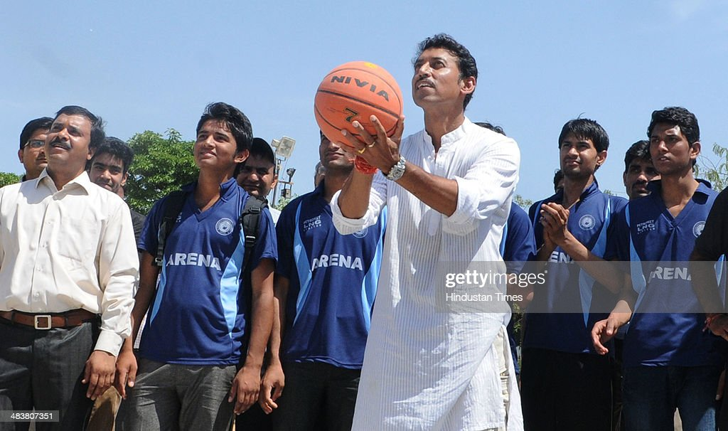 BJP Lok Sabha candidate for Jaipur Rural Constituency, Colonel Rajyavardhan Singh Rathore tries his basketball skills while interacting with students at a dental college while campaigning in Kukas village on Thursday, April 10, 2014 in Jaipur, India.