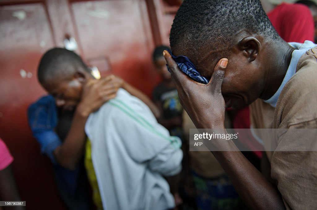 Lokuli Loleko Felicien, 24, (R) reacts to finding the body of his father in the Ndosho district of Goma in the east of the Democratic Republic of the Congo on November 21, 2012. Lokuli's father, a government military doctor, was killed in fighting yesterday between the government army and M23 rebels as they took the provincial capital. Lokuli and his two brothers came across his father's body by chance in the western district of Goma, having searched in the morgue and a hospital yesterday evening. The lightning seizure by rebels of Democratic Republic of Congo's city of Goma is a blow for President Joseph Kabila, but how far fighters will press forward their advantage is not clear, analysts say. AFP PHOTO/PHIL MOORE