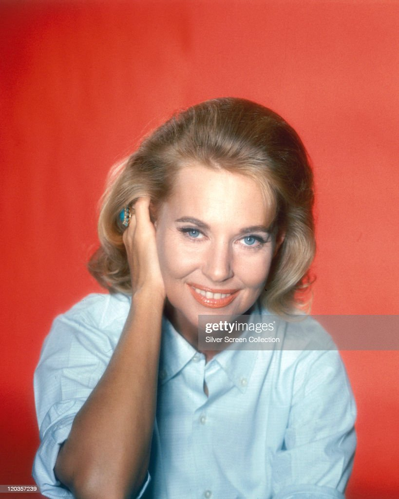 ... in a studio portrait, against a red background, circa 1960. Show more