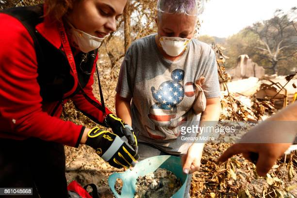 Lola Cornish center and her daughter Kat Corazza look over recovered family jewels that survived the fire and destruction of Cornish's grandfather's...