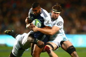 Lolagi Visinia of the Blues is tackled by Stephan Lewies of the Sharks during the round 15 Super Rugby match between the Blues and the Sharks at...