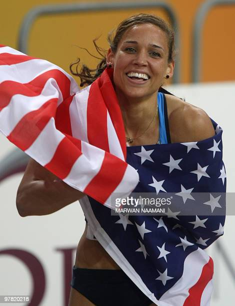 US Lolo Jones celebrates her gold medal with a national flag at the end of the women's 60m hurdles final at the 2010 IAAF World Indoor Athletics...