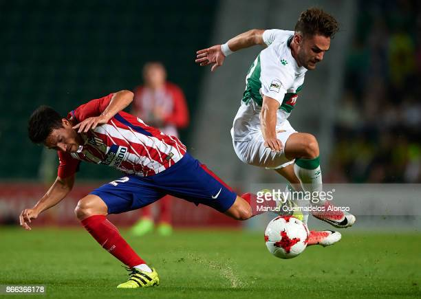 Lolo of Elche competes for the ball with Nico Gaitan of Atletico de Madrid during the Copa del Rey first leg match between Elche CF and Atletico de...