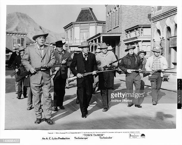 Lon Chaney Jr and group of armed men walking into the town square in a scene from the film 'Town Tamer' 1965