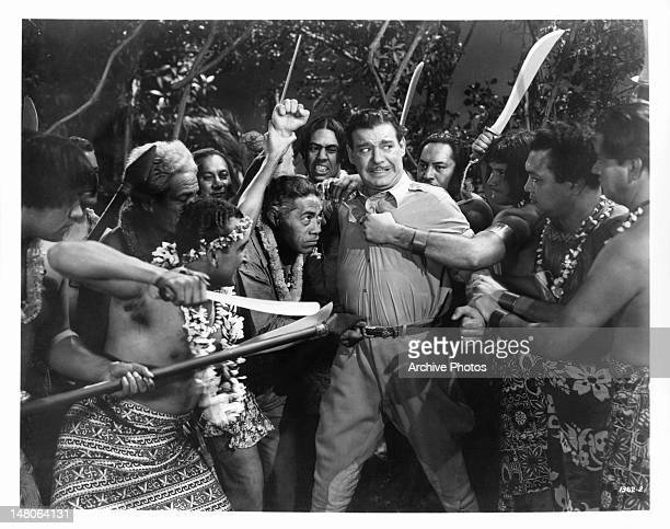 Lon Chaney Jr is crowded by a native tribe with swords pointed directly at him in a scene from the film 'Weird Woman' 1944