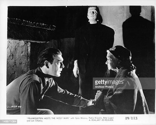 Lon Chaney Jr touching the hand of woman as Bela Lugosi as the monster standing the background in a scene from the film 'Frankenstein Meets The Wolf...