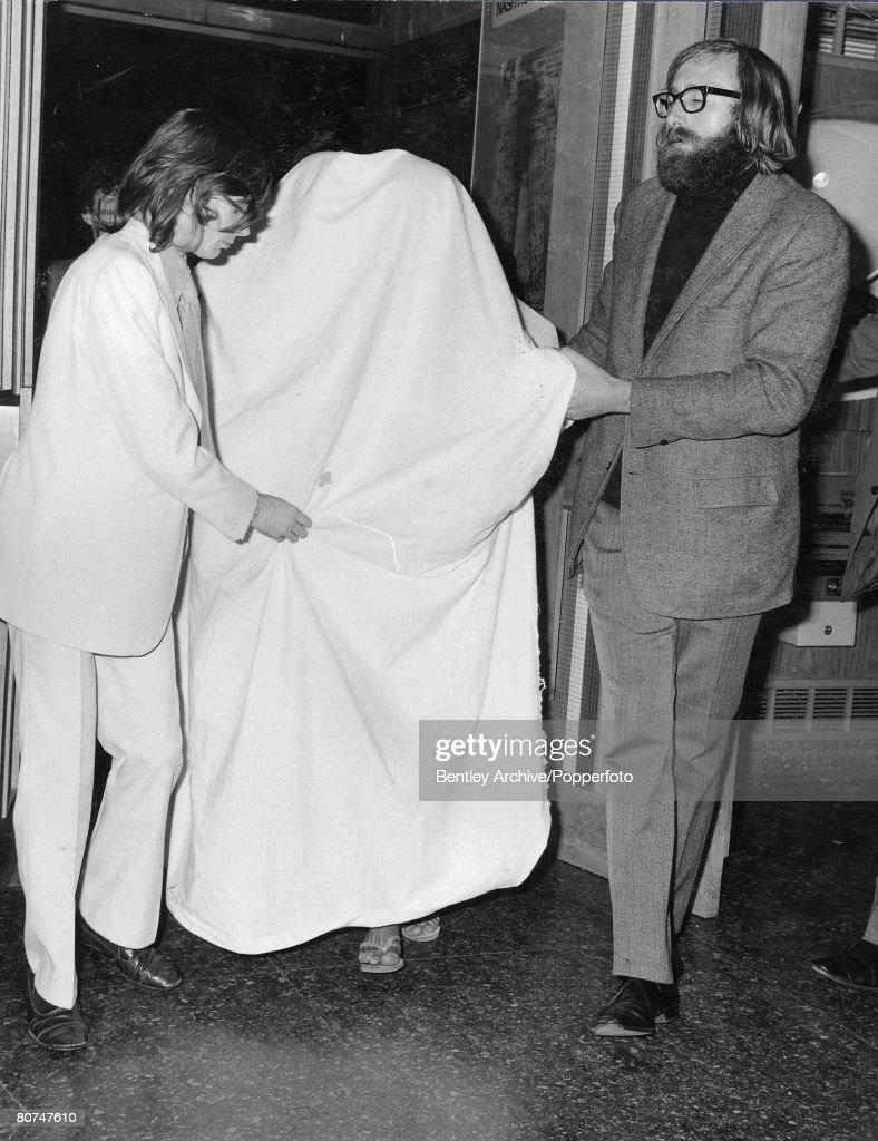 London 11th September A couple said to be pop star John Lennon and wife Yoko Ono leave the Institute of Contemporary Arts under a white sack after...