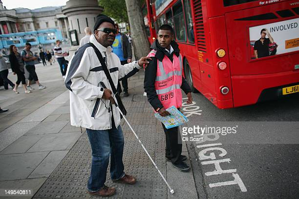 A 'London 2012 Gamestime travel' member of staff assists a visually impaired man in Trafalgar Square on July 30 2012 in London England London's...