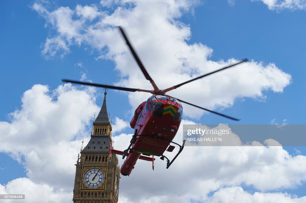 A London air ambulance takes off from Parliament Square in front of the Houses of Parliament after it arrived earlier as part of the response to an incident in which a man was injured after falling 15 feet at nearby Westminster Bridge in London on May 3, 2016. The man was taken to hospital by road ambulance. / AFP / NIKLAS HALLE'N