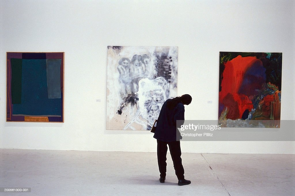 UK, London, Atlantis Gallery, person looking at artwork, rear view : Stock-Foto