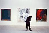 UK, London, Atlantis Gallery, person looking at artwork, rear view