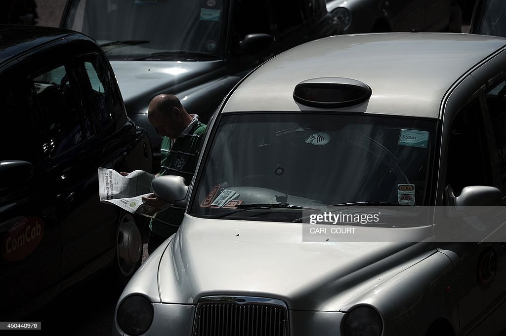 A London black cab driver reads a newspaper during a protest against a new private taxi service 'Uber', a mobile phone app, in central London on June 11, 2014. Taxi drivers brought parts of London, Paris and other European cities to a standstill on June 11 as they protested against new private cab apps such as Uber which have shaken up the industry. Thousands of London's iconic black cabs, many of them beeping their horns, filled the roads around Buckingham Palace, Trafalgar Square and the Houses of Parliament to the exclusion of any other vehicles.