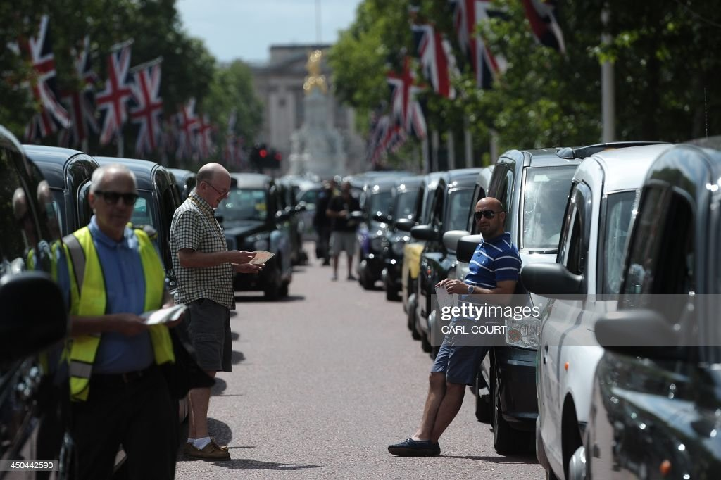 London black cab drivers take part in a protest against a new private taxi service 'Uber', a mobile phone app, on the Mall leading to Buckingham Palace in central London on June 11, 2014. Taxi drivers brought parts of London, Paris and other European cities to a standstill on June 11 as they protested against new private cab apps such as Uber which have shaken up the industry. Thousands of London's iconic black cabs, many of them beeping their horns, filled the roads around Buckingham Palace, Trafalgar Square and the Houses of Parliament to the exclusion of any other vehicles. AFP PHOTO / CARL COURT