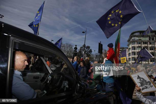 A London black taxi cab waits as protesters carry European Union flags rally during a Unite for Europe march to protest Brexit in central London UK...