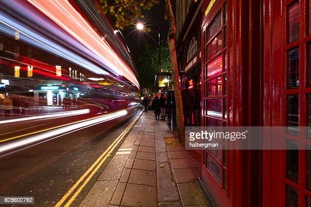 London Bus Streaking Past Phone Boxes