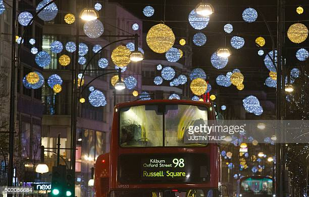 London buses pass under Christmas lights on Oxford Street in central London on December 20 on the final shopping Sunday before Christmas AFP PHOTO /...