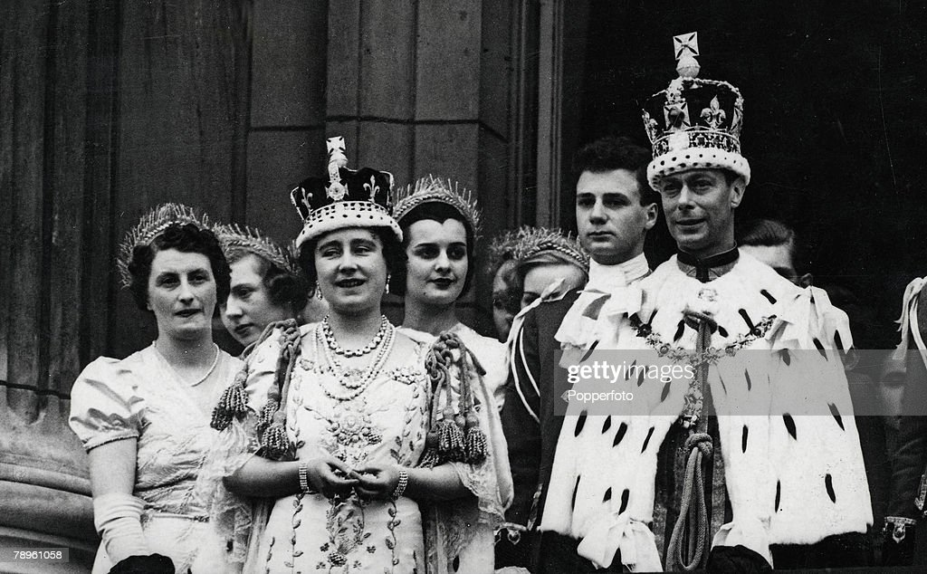 London, England, 12th May 1937, King George VI and Queen Elizabeth (the Queen Mother) pictured wearing their crowns and coronation robes as they stand on the balcony of Buckingham palace after their coronation in 1937