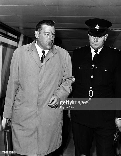 London England 12th October 1970 Northern Ireland protestant leader Reverand Ian Paisley is escorted to his car upon arrival at Heathrow airport from...
