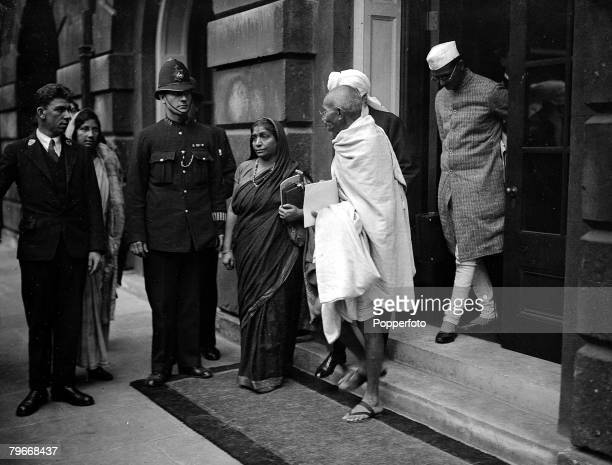London England 16th September Indian spiritual leader Mahatma Gandhi talking to poetess Mrs Naidu who is seen calling a taxi for the Indian leader as...