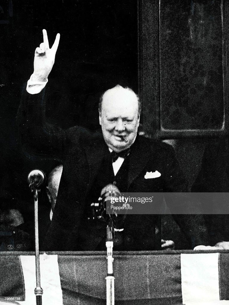 London, England, 8th May, 1945, British Prime Minister Winston Churchill gives the famous V sign (victory sign) to large crowds gathered in Whitehall and Parliament Square from the balcony of the Ministry of HEalth on the evening of VE Day at the end of World War Two