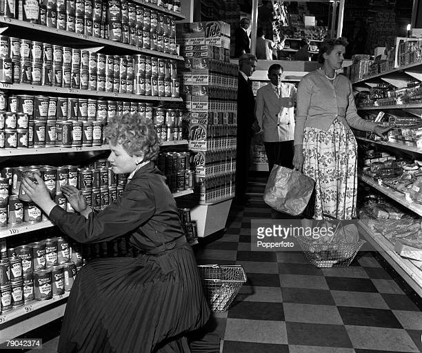 London England A general view of the Richmond Supermarket showing a woman stacking shelves as a customer browses the aisles Behind them is the...