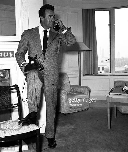 London England American actor Gilbert Roland is pictured talking on the telephone at the Savoy Hotel