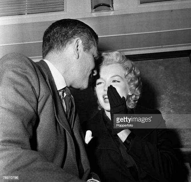 London England American actress Marilyn Monroe is pictured at a press reception at the Savoy Hotel whispering to British actor Laurence Olivier