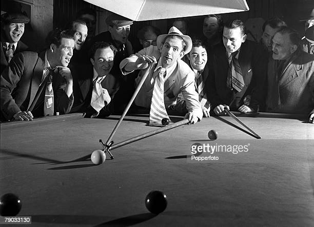 London England British actor and comedian Arthur English is pictured dressed as a 'spiv' as he plays snooker with a rest