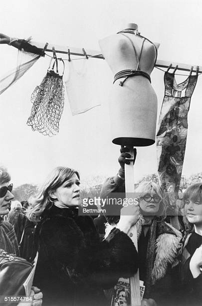 London feminists carry a cross decorated with a female torso and objects from domestic life They march for equal pay and expanded rights and...