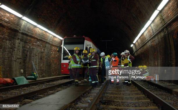 London firefighters carry a model pretending to be a survivor out of a crashed tram during a training exercise in Croydon South London