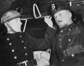 A London fireman of the Auxiliary Fire Service tries on an American helmet during a visit to a New York fire station 19th August 1941 The AFS was a...