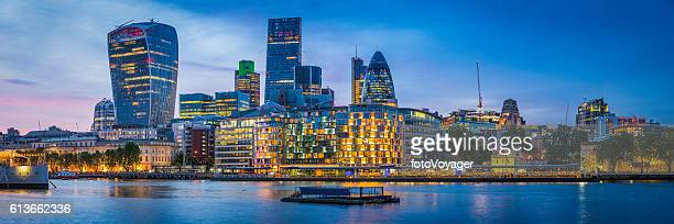 London futuristic skyscrapers glittering at sunset overlooking River Thames UK