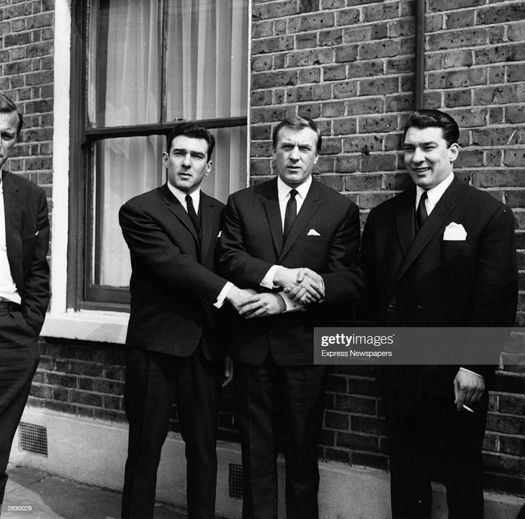 London gangster twins Ronald (right) and Reginald Kray (left) link hands with their brother Charles (centre) after the twins had been found not guilty on a menaces charge. They were tried and convicted at the Old Bailey in 1969. Original Publication: People Disc - HU0166