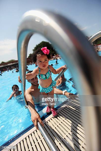 London Gomez stands on a ladder on opening day of the newly renovated McCarren Park Pool on June 28 2012 in the Brooklyn borough of New York City The...