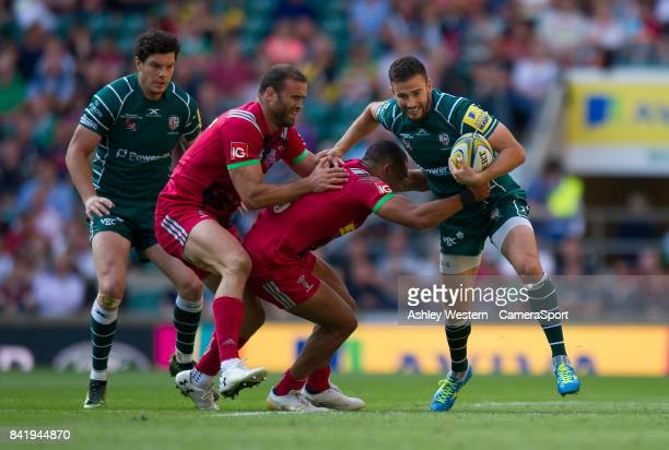 London Irish's Tommy Bell evades the tackle of Harlequins' Joe Marchant during the Aviva Premiership match between London Irish and Harlequins at...
