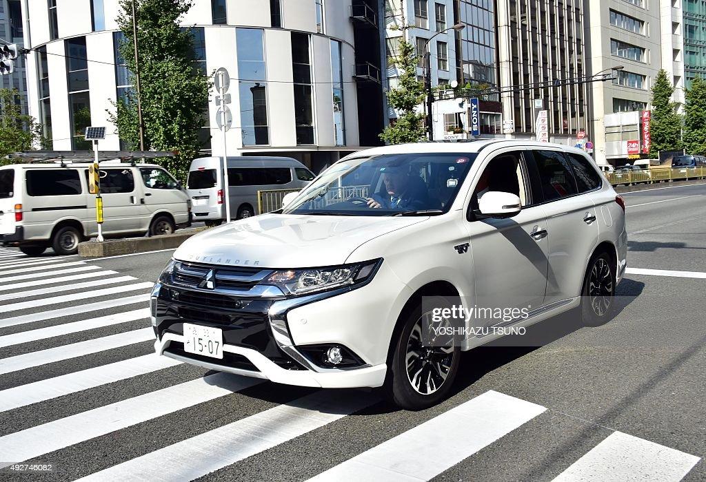 London Mayor Boris Johnson drives the Mitsubishi Motors plugin hybrid vehicle 'Outlander PHEV' near the MMC headquarters in Tokyo on October 15 2015...
