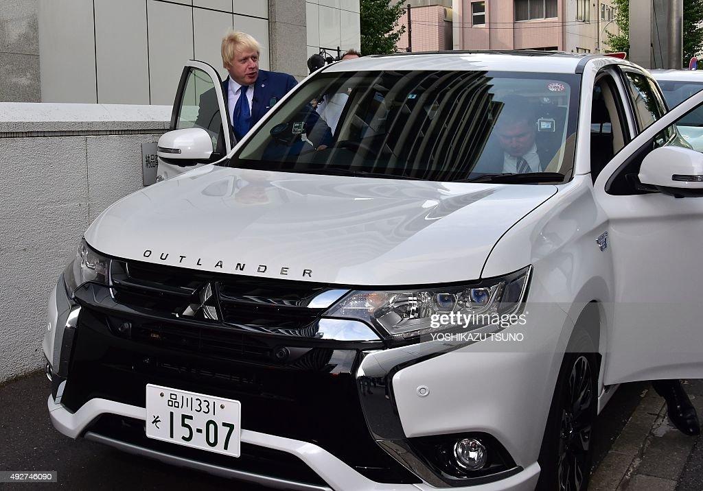 London Mayor Boris Johnson gets into the Mitsubishi Motors plugin hybrid vehicle 'Outlander PHEV' near the MMC headquarters in Tokyo on October 15...