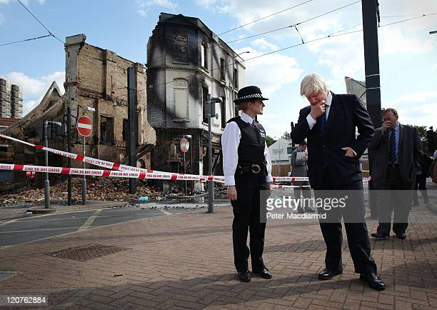London Mayor Boris Johnson stands with Police Superintendent Jo Oakley near burnt out Reeves Corner furniture store on August 9 2011 in Croydon...