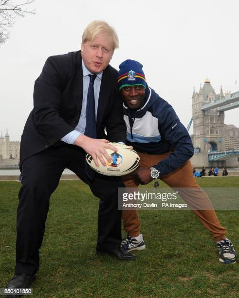 London Mayor Boris Johnson takes a 'Big Hit' for London from RLWC2013 ambassador Martin Offiah during a photocall at Tower Bridge London
