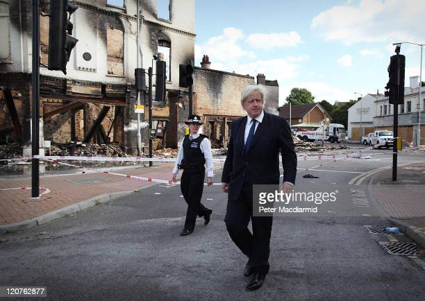 London Mayor Boris Johnson walks with Police Superintendent Jo Oakley near burnt out Reeves Corner furniture store on August 9 2011 in Croydon...