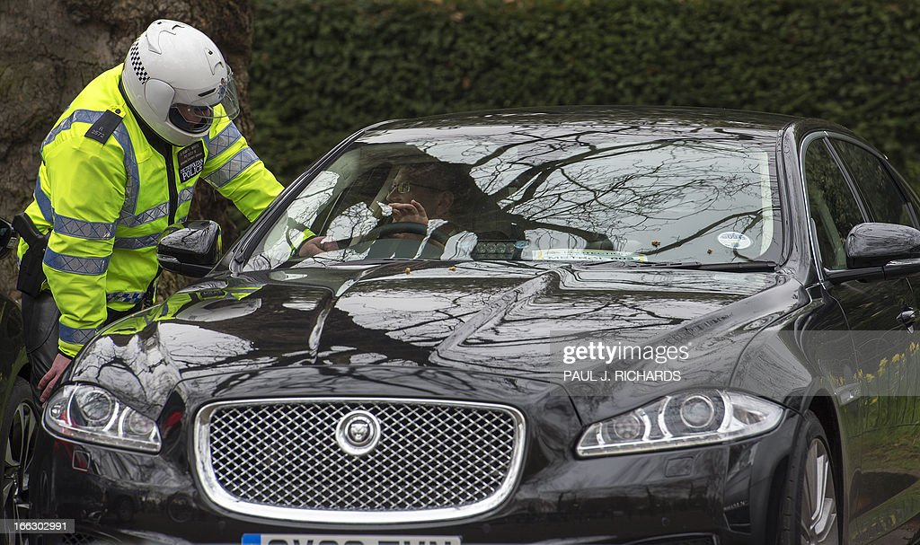 A London Metropoliton Police Officer speaks with the driver of a new model Jaguar XF motorcar on the streets of London near Buckingham Palace April 11, 2013. AFP Photo/Paul J. Richards