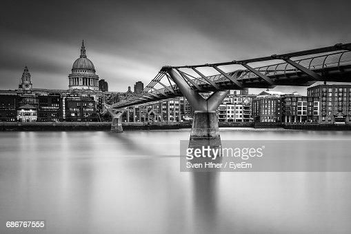 London Millennium Footbridge Over Thames River By St Paul Cathedral Against Sky
