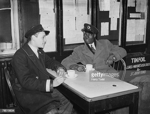 London Passenger Transport Board lorry drivers B Johnston of Bermuda and J Joof from The Gambia enjoy a chat over a cup of tea in a canteen 17th...